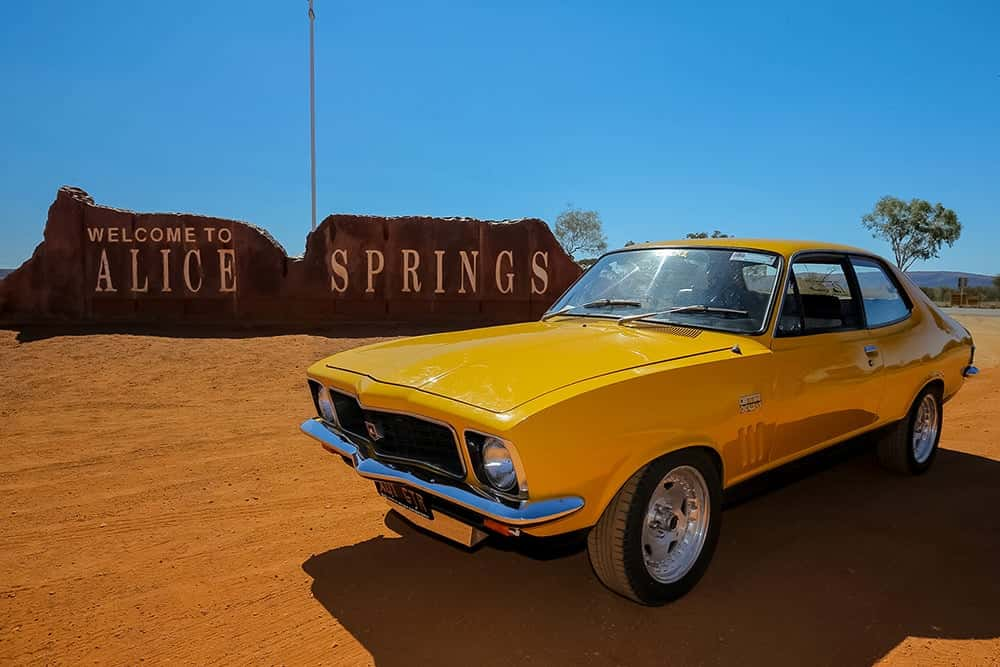 Red CentreNATS - Yellow car in front of Alice Springs sign